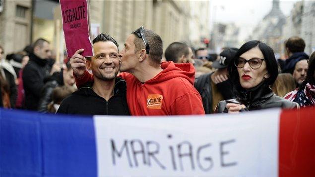 Un homme embrasse son compagnon durant la manifestation pour le projet de loi permettant le mariage et l'adoption pour les gais, à Paris.