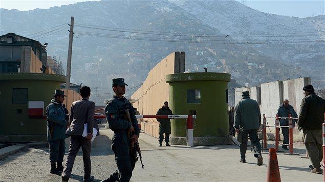 Des membres des forces de sécurité montent la garde devant le quartier général de la police à Kaboul, où un consultant a été abattu par une policière afghane