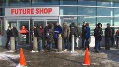 Des consommateurs attendent l'ouverture des magasins.