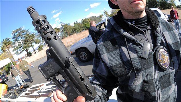 Un policier vient de récupérer une arme d'assaut lors de l'opération à Los Angeles