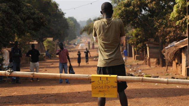 Un homme bloque une route menant à la capitale en prévision d'une éventuelle offensive des rebelles à Bangui.
