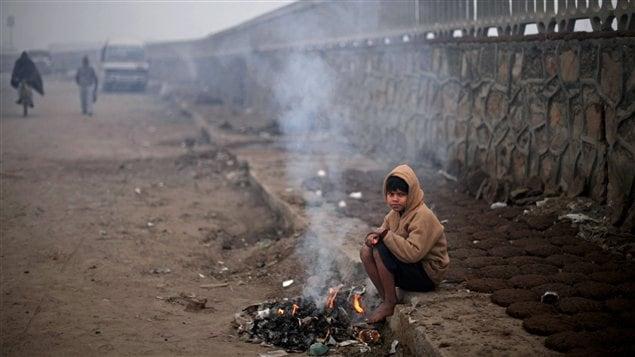Un garçon tente de se garder au chaud à New Delhi, en Inde, une région qui fait face à une vague de froid d'une rare intensité