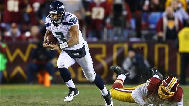 Le quart des Seahawks de Seattle Russell Wilson fait mordre la poussière à Barry Cofield des Redskins de Washington.