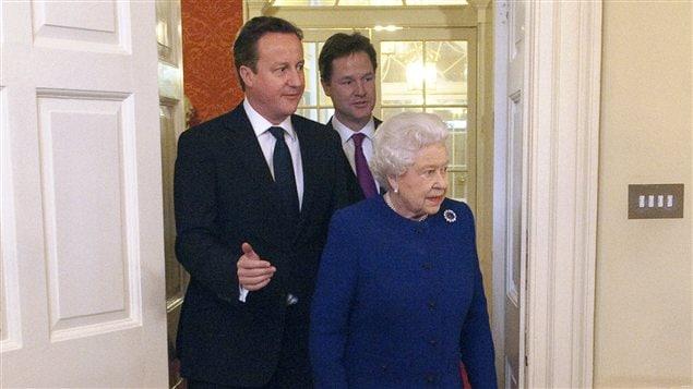 Le premier ministre britannique David Cameron et le vice-premier ministre Nick Clegg accompagnent la Reine Élisabeth II lors de sa première visite à la résidence du premier ministre, au 10 Downing Street, le 18 décembre 2012.