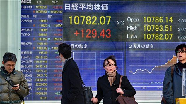 Des Japonais marchent devant un écran montrant les cours de la bourse, alors que le gouvernement vient d'annoncer une plan de relance économique