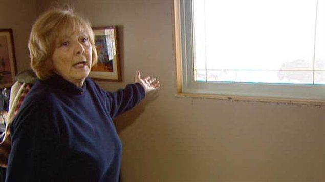 Lydia Grubert montrant une fenêtre dont l'installation est inachevée dans sa maison de Twin Lakes Beach endommagée par les inondations de 2011.