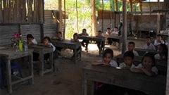 Des élèves de l'école élémentaire de Pakxoun, au Laos, sont assis dans leur bâtiment décrépi.