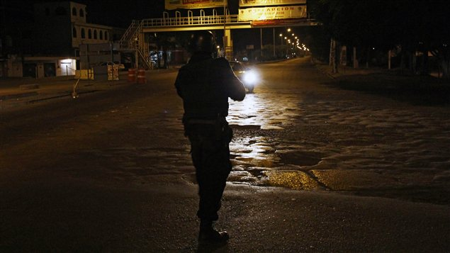 Un policier mexicain pointe son arme vers un véhicule transportant un présumé trafiquant de drogues