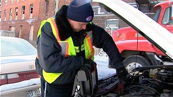 Un technicien du CAA procède au survoltage d'une voiture.