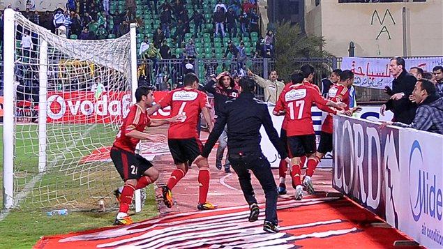 Des joueurs fuient le stade alors que les partisans commencent à s'affronter sur le terrain, le 1er février 2012