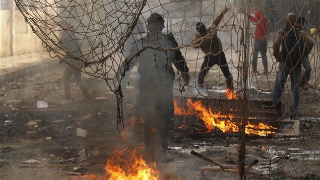 Des protestataires jettent des pierres aux policiers lors d'une manifestation à la place Tahrir samedi.