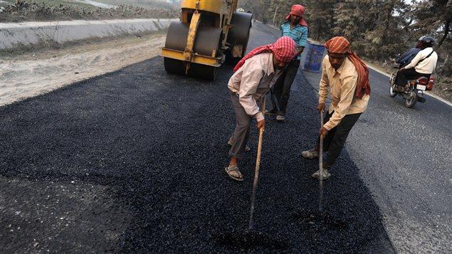 Des travailleurs indiens asphaltent une route.