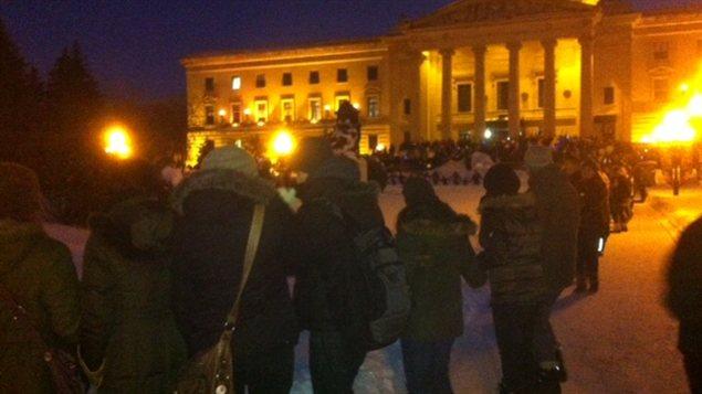 Un grand nombre de personnes prennent part une danse en cercle devant le palais législatif du Manitoba à Winnipeg, le 28 janvier 2013, dans le cadre du mouvement Idle No More.