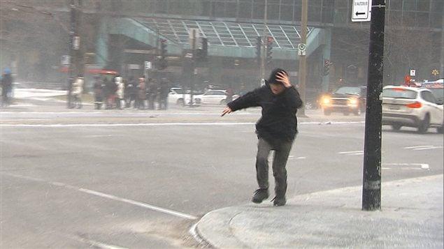 Une puissante bourrasque de vent malmène un piéton au centre-ville de Montréal.