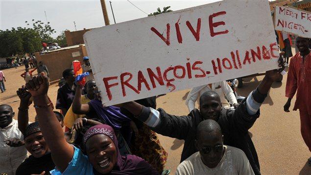 Des Maliens brandissent des pancartes remerciant le président français, à Ansongo, proche de la frontière avec le Niger.