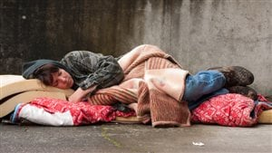 Une sans-abris dort par terre.
