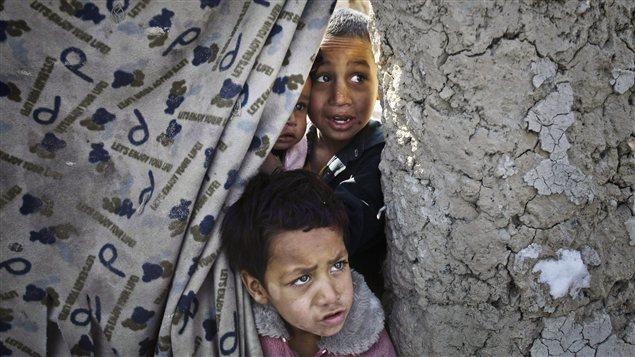 Des enfants attendent de l'aide humanitaire dans un camp de réfugiés de Kaboul, en Afghanistan.