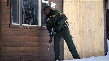 Un policier à la recherche de Christopher Dorner regarde à l'intérieur d'une maison de Big Bear Lake, en Californie.