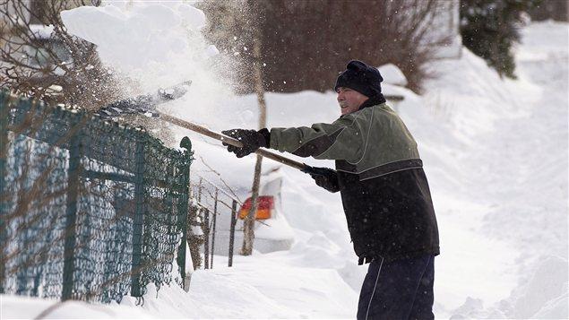 Un habitant de Dartmouth, en Nouvelle-Écosse, déneige devant sa résidence.