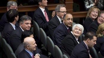 Les nouveaux ministres de l'Ontario regardent vers la mezzanine de l'Assemblée législative durant leur cérémonie d'assermentation, le 11 février 2013.