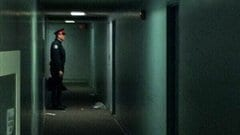 Un agent de la Police de Toronto surveille la porte de l'appartement où un jeune de 15 ans a été abattu tard le 11 février 2013.