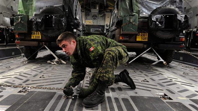 Un militaire canadien s'assure de bien immobiliser des jeeps français à l'intérieur de l'avion de transport CC-177 fourni par le Canada pour la mission au Mali.
