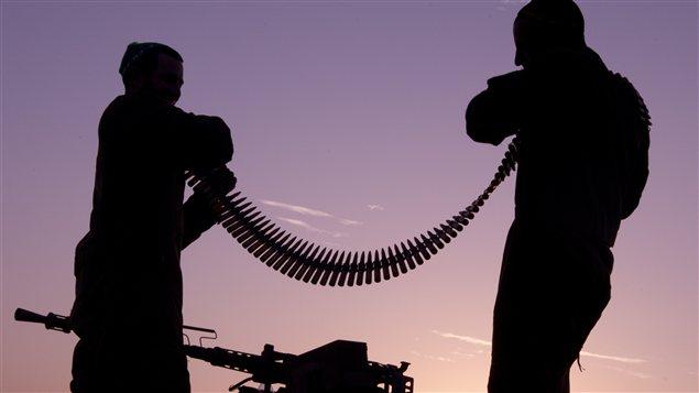 Des soldats examinent une ceinture de balles.