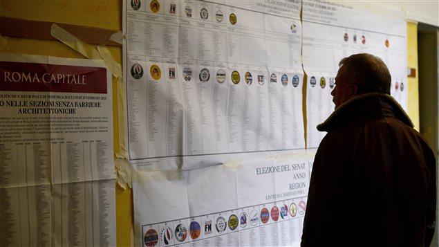 Un Italien regarde des informations sur les élections dans un bureau de vote, le 24 février.