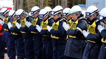Des policiers japonais respectent une minute de silence alors qu'ils recherchent toujours des victimes du tsunami du 11 mars 2011, à Ishinomaki