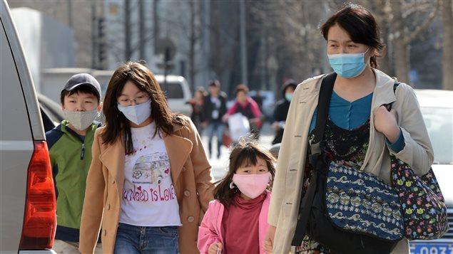 Les membres d'une famille chinoise portent des masques pour se protéger de la pollution de l'air, le 27 mars 2013.