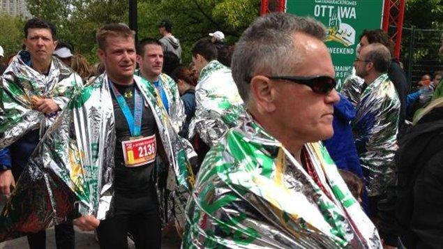 Des coureurs fiers d'avoir terminé le marathon d'Ottawa.