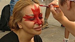 Une jeune fille se fait maquiller une feuille d'érable sur le visage lors de la fête du Canada à Ottawa.