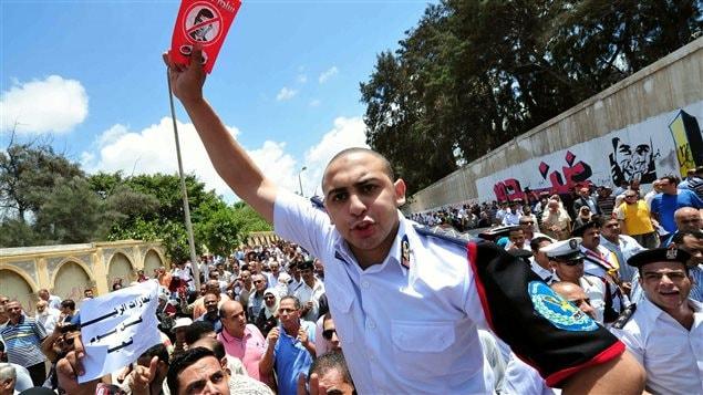 Un policier brandit un carton rouge anti-Morsi pendant une manifestation à Alexandrie, dimanche le 1er juillet 2013