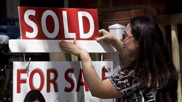 Une agente ajoute la mention « Vendu » à une affiche d'un immeuble à vendre à Toronto