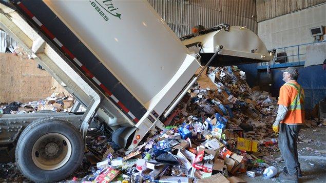Un employé assiste au dépôt des déchets à trier au centre de tri de Rouyn-Noranda