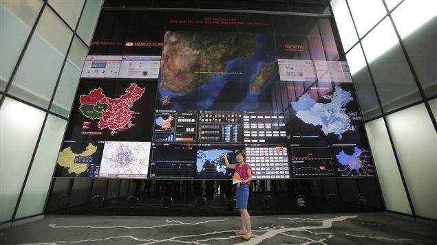 Une employée du géant local du commerce électronique Alibaba, basé en Chine, explique le fonctionnement de l'écran géant à l'entrée du siège social de l'entreprise.