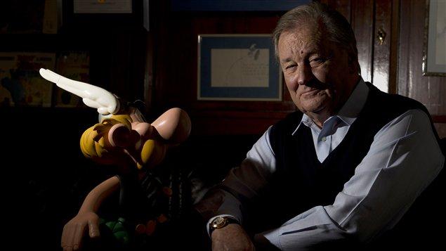 Albert Uderzo pose à côté d'une figurine de son célèbre personnage Astérix, en octobre 2013.