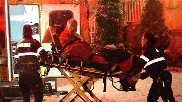 Le Dr Alain Sirard transporté en ambulance
