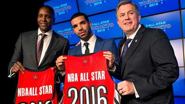Drake (au centre) entouré du directeur général des Raptors, Masai Uriji (gauche), et du PDG de MLSE Tim Leiweke (droite) lorsque le rappeur a été fait ambassadeur de l'équipe en septembre.