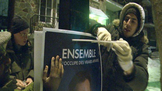 Des bénévoles procèdent à l'installation d'une pancarte électorale.