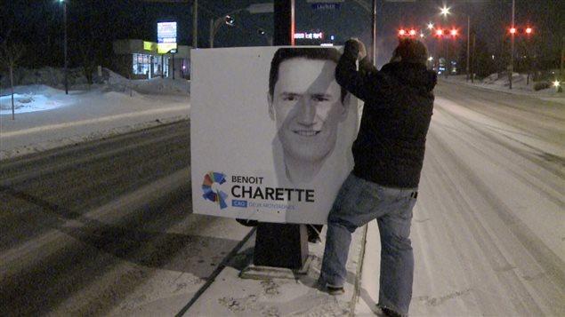 Un poseur d'affiches à l'oeuvre à Deux-Montagnes quelques heures avant l'annonce officielle des élections.