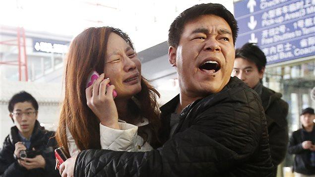 Des proches d'un passager du vol de la compagnie Malaysia Airlines apprennent la mauvaise nouvelle, à l'aéroport de Pélin, samedi.