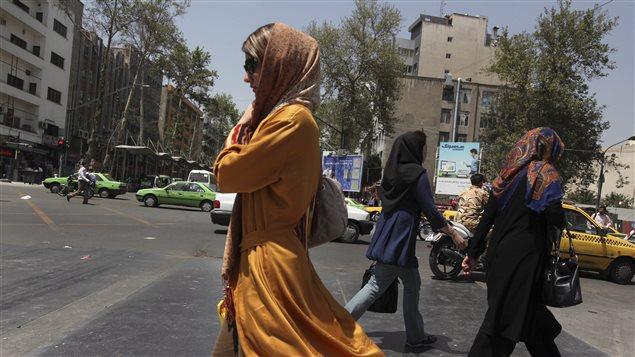 Des femmes traversent la rue à Téhéran lors des élections de 2013.