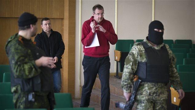 Des hommes cagoulés ont escorté les membres de l'OSCE qui ont pris part à une conférence de presse à Slaviansk, le 27 avril