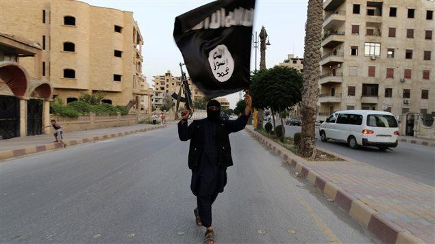 Un militant de l'État islamique brandit un drapeau du «califat» dans la ville syrienne de Saqqa.