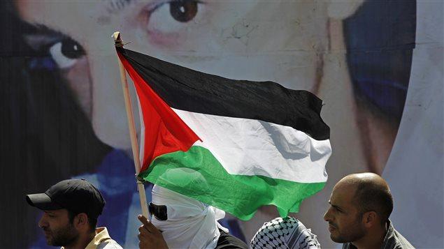 Des Palestiniens devant une affiche montrant l'adolescent Mohamed Abou Khoudaïr, le 4 juillet 2014