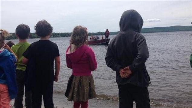 Les enfants apprécient le lâché de milliers de truites dans le lac Mégantic.