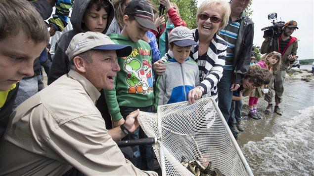 La mairesse de Colette Roy-Laroche est des enfants relâchent des truites dans le lac Mégantic.