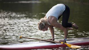 Une femme exerce une position de yoga sur une planche de surf.