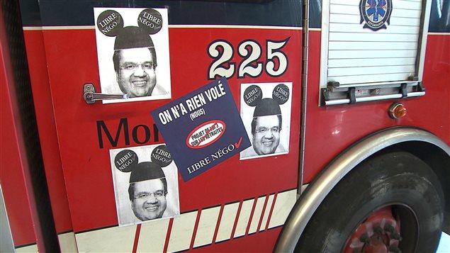 Des camions de pompiers de la Ville de Montréal tapissés d'autocollants de protestation.